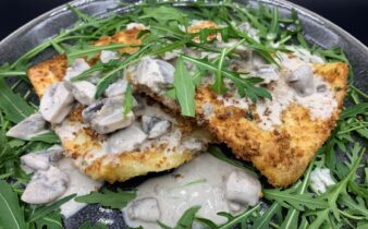 Panko paneret ravioli med spinat og ricotta serveret med mild champignon sauce og rucola